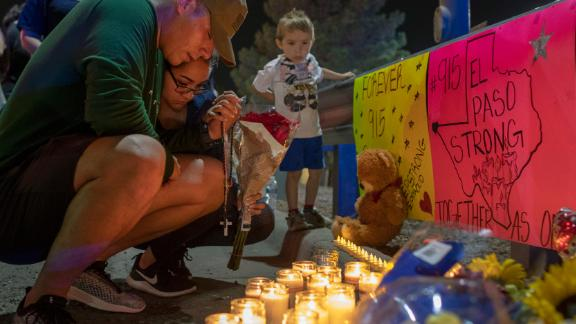 Rene Aguilar and Jackie Flores pray at a makeshift memorial for the victims of Saturday's mass shooting at a shopping complex in El Paso, Texas, Sunday, August 4, 2019. (AP Photo/Andres Leighton)