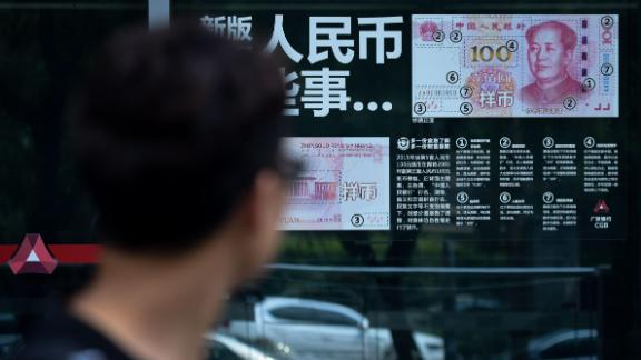 A man looks at information posted on a bank door showing how to distinguish real banknotes in Beijing on July 20, 2018. - China