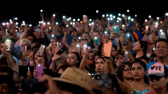 People hold up their phones during a prayer and candle vigil organized by the city, after a shooting left 20 people dead at the Cielo Vista Mall Wal-Mart in El Paso, Texas, on August 4, 2019. - The United States mourned Sunday for victims of two mass shootings that killed 29 people in less than 24 hours as debate raged over whether President Donald Trump