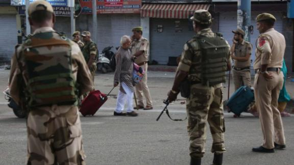Tourists walk past Indian security forces during curfew like restrictions in Jammu, India, Monday, Aug. 5, 2019. An indefinite security lockdown was in place in the Indian-controlled portion of divided Kashmir on Monday, stranding millions in their homes as authorities also suspended some internet services and deployed thousands of fresh troops around the increasingly tense region. (AP Photo/Channi Anand)