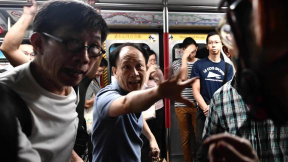 A train passenger gestures toward a protester, right, who was preventing the doors of a train from closing on August 5. The protester was trying to disrupt Hong Kong