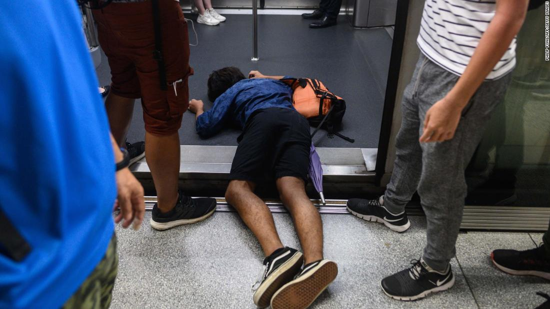 A man lies down on an underground train during a protest on August 5.
