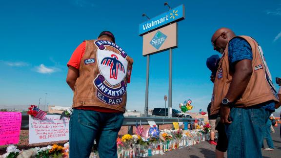 """A chaplain (R) from a motorcycle group prays with friends at a makeshift memorial after the shooting that left 21 people dead at the Cielo Vista Mall WalMart in El Paso, Texas, on August 5, 2019. - US President Donald Trump on Monday urged Republicans and Democrats to agree on tighter gun control and suggested legislation could be linked to immigration reform after two shootings left 30 people dead and sparked accusations that his rhetoric was part of the problem. """"Republicans and Democrats must come together and get strong background checks, perhaps marrying this legislation with desperately needed immigration reform,"""" Trump tweeted as he prepared to address the nation on two weekend shootings in Texas and Ohio. """"We must have something good, if not GREAT, come out of these two tragic events!"""" Trump wrote. (Photo by Mark RALSTON / AFP)        (Photo credit should read MARK RALSTON/AFP/Getty Images)"""