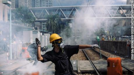 A protester throw a stone towards police outside Tin Shui Wai police station during a protest on August 05, 2019 in Hong Kong.