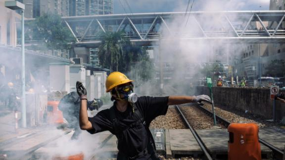 A protester throws a stone towards police outside Tin Shui Wai police station during a protest on August 5, 2019 in Hong Kong.