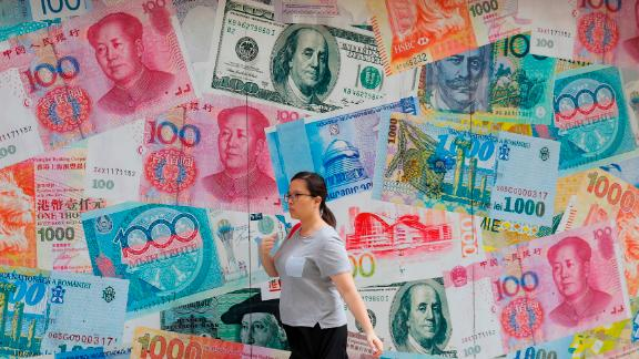 A woman walks by a money exchange shop decorated with different countries currency banknotes at Central, a business district in Hong Kong, Tuesday, Aug. 6, 2019. China