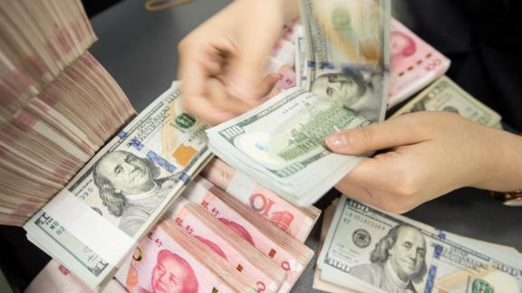 """A Chinese bank employee counts 100-yuan notes and US dollar bills at a bank counter in Nantong in China's eastern Jiangsu province on August 6, 2019. - The Chinese currency steadied on August 6, a day after Beijing let the yuan weaken against the dollar, sending markets into freefall and leading the US to formally designate China a """"currency manipulator"""". (Photo by STR / AFP) / China OUT        (Photo credit should read STR/AFP/Getty Images)"""