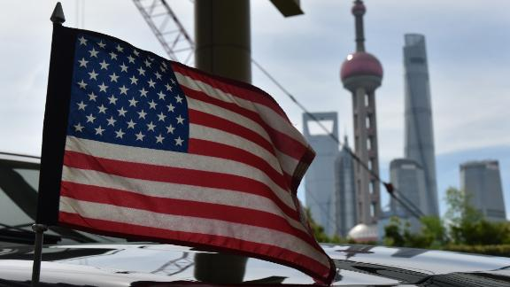 A US flag flies on a US consulate car with the backdrop of buildings in the Lujiazui financial district, outside a hotel where US trade negotiators are staying in Shanghai on July 31, 2019. - US and Chinese negotiators are holding talks aimed at resolve their year-long trade war after President Donald Trump warns China that getting a deal would be tougher if it waits for next year