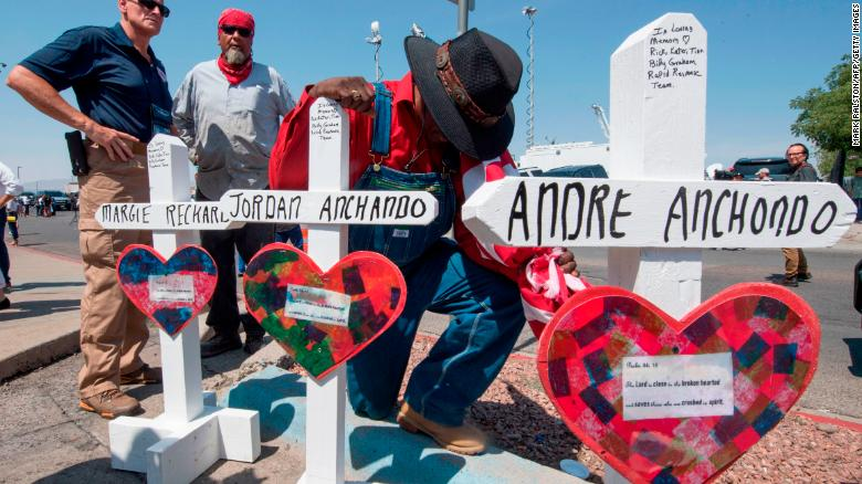 A man prays beside crosses with the names of Jordan and Andre Anchondo and the other victims of the El Paso massacre.