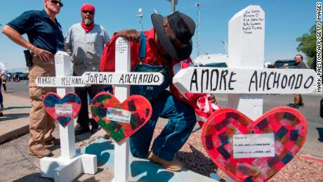 A man prays beside crosses with the names of Jordan and Andre Anchondo, and the other victims of the El Paso massacre.