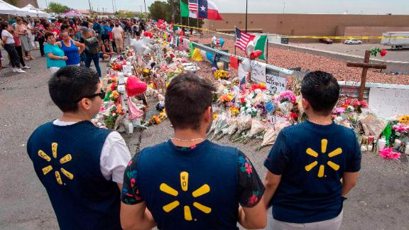 Walmart employees pay their respects at a makeshift memorial for the shooting victims, at the Cielo Vista Mall Walmart in El Paso, Texas, on August 6, 2019. - The August 3 shooting left 22 people dead. US President Donald Trump will visit the Texan border city August 7, and will also travel to Dayton, Ohio where a second mass shooting early August 4 left another nine dead. (Photo by Mark RALSTON / AFP)        (Photo credit should read MARK RALSTON/AFP/Getty Images)