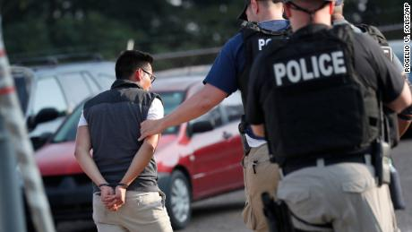 A man is taken into custody at a Koch Foods Inc. plant in Morton, Miss., on Wednesday, Aug. 7, 2019. U.S. immigration officials raided several Mississippi food processing plants on Wednesday and signaled that the early-morning strikes were part of a large-scale operation targeting owners as well as employees.