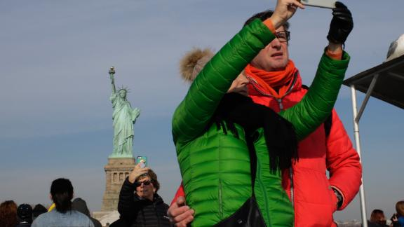 Tourists take pictures as a cruise passes the Statue of Liberty on January 21, 2018, in New York.