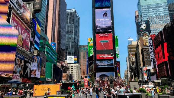 People walk around Times Square in New York City on July 9, 2019.