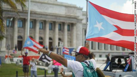 A demonstrator waves a flag outside the capitol building in San Juan, Puerto Rico, on August 2, 2019.