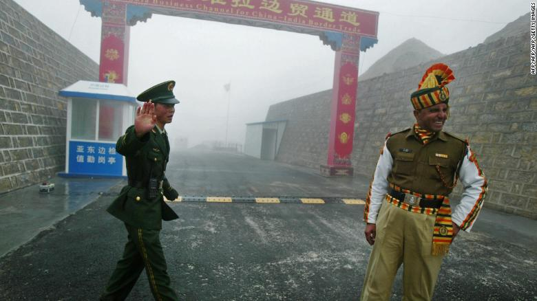 Guards stand at the India-China border. India's leaders may look to China's policies in Xinjiang and Tibet to control Kashmir.
