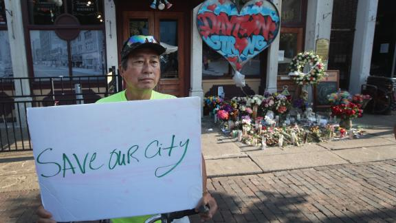 Luong Vo shares a message near a memorial in the Oregon District, where a mass shooting early Sunday morning left nine dead and 27 wounded, on August 07, 2019 in Dayton, Ohio. President Donald Trump visited the city today to offer his support to the community. The shooting happened less than 24 hours after a gunman in Texas opened fire at a shopping mall in El Paso killing 22 people.