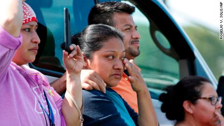 Friends, coworkers and family watch as U.S. immigration officials raid a plant in Morton, Mississippi.