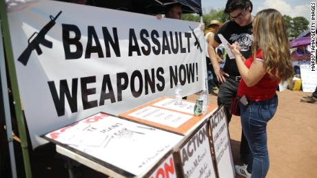 A 'Ban Assault Weapons Now' sign is displayed near a voter registration table at a protest against President Trump's visit on August 7, 2019 in El Paso, Texas.