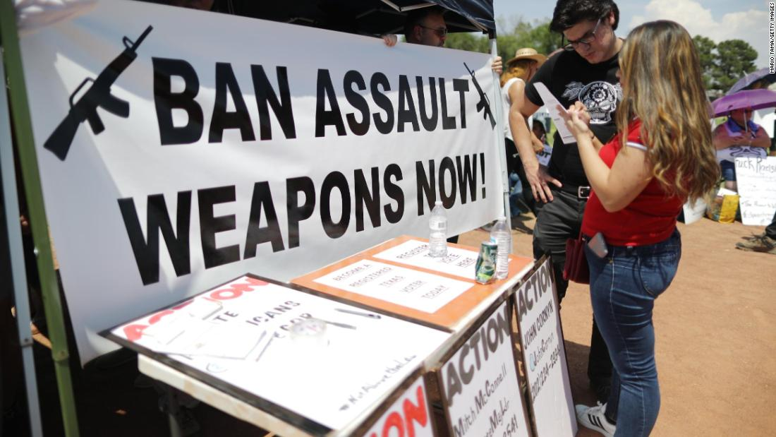 "A ""Ban Assault Weapons Now"" sign is displayed near a voter registration table in El Paso."