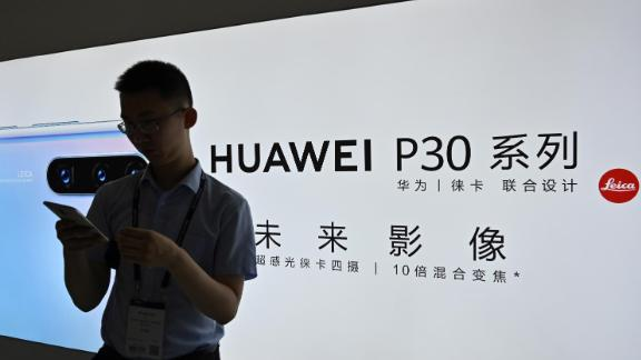 A man looks at his smartphone at a Huawei stand during the Mobile World Congress 2019.