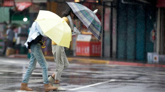Two Taiwanese women face powerful gusts of wind generated by Typhoon Lekima in Taipei, Taiwan, on August 9, 2019.