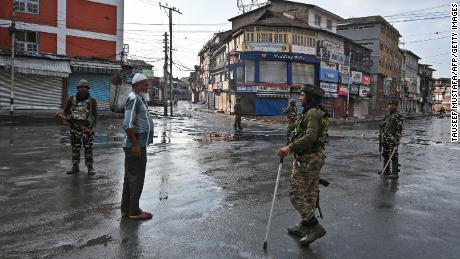 Indian security personnel question a man on a street during a curfew in Srinagar on August 8, 2019, as widespread restrictions on movement and a telecommunications blackout remained in place after the Indian government stripped Jammu and Kashmir of its autonomy. (Photo by Tauseef MUSTAFA / AFP)        (Photo credit should read TAUSEEF MUSTAFA/AFP/Getty Images)