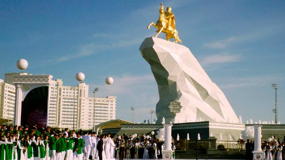 People gather for the unveiling ceremony of a 21-meter, gold-leaf statue of President Gurbanguly Berdymukhamedov atop a horse mounted on a towering pile of marble in Ashgabat, Turkmenistan, in 2015.