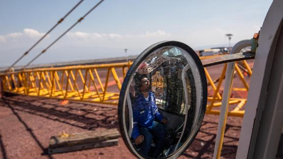 A worker is reflected in the mirror of a machine as cranes are removed from the New International Airport of Mexico City (NAICM) in Texcoco, Mexico.