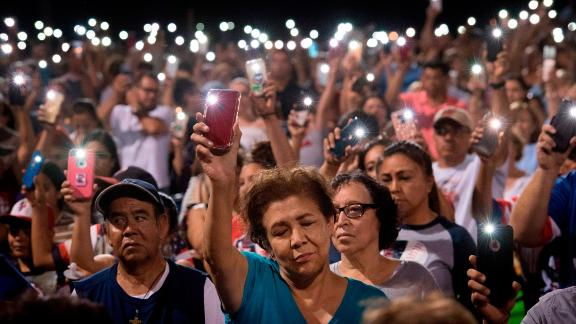 TOPSHOT - People hold up their phones during a prayer and candle vigil organized by the city, after a shooting left 20 people dead at the Cielo Vista Mall Wal-Mart in El Paso, Texas, on August 4, 2019. - A shooting at a Walmart store in Texas left multiple people dead. At least one suspect was taken into custody after the shooting in the border city of El Paso, triggering fear and panic among weekend shoppers as well as widespread condemnation. It was the second fatal shooting in less than a week at a Walmart store in the US and comes after a mass shooting in California last weekend. (Photo by Mark RALSTON / AFP)        (Photo credit should read MARK RALSTON/AFP/Getty Images)
