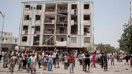 People gather at the site of a deadly attack on the Sheikh Othman police station, in Aden, Yemen, Thursday, Aug. 1, 2019. Yemen's rebels fired a ballistic missile at a military parade Thursday in the southern port city of Aden as coordinated suicide bombings targeted the police station in another part of the city. The attacks killed over 50 people and wounded dozens. (AP Photo/Nariman El-Mofty)