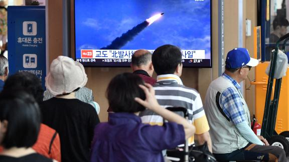 People watch a television news screen showing file footage of a North Korean missile launch this month.