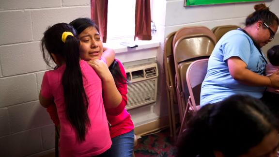 Sisters hug in the Trinity Mission Center in Forest, Mississippi, after their father was detained by ICE agents.