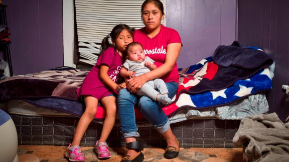 August 9, 2019 - Forest, Mississippi: Undocumented Guatemalan immigrant Isabella Gregorio Alonzo, 27, poses for a portrait with her daughters Juana, 7, and Angelina, 3 months, in the home she shares with other immigrants in Forest, Mississippi. Both Alonzo and her husband were detained by ICE agents during raids of food procession facilities in Mississippi on August 7, 2019. Alonzo was released with an ankle monitor, which can be seen on her right leg.