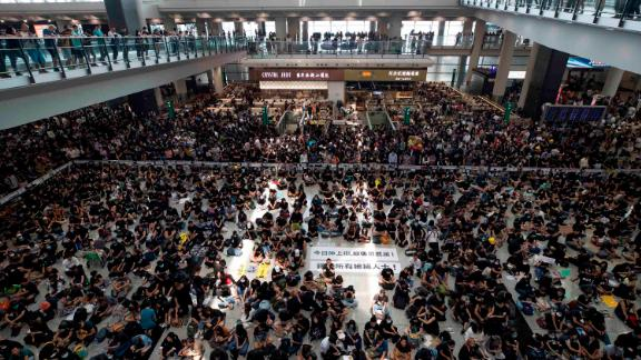 """Protesters surround banners that read: """"Those charge to the street on today is brave!,"""" center top, and """"Release all the detainees!"""" during a sit-in rally at the arrival hall of the Hong Kong International airport, Monday, Aug. 12, 2019. Hong Kong police showed off water cannons Monday as pro-democracy street protests stretched into their 10th week with no sign of either side backing down. (AP Photo/Vincent Thian)"""