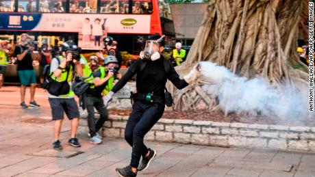 A protester in Hong Kong throws tear gas back at police amid scuffles in Tsim Sha Tsui, a major shopping district, on August 11, 2019.