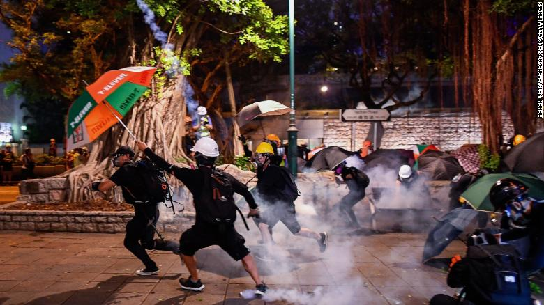 Pro-democracy protesters throw back tear gas cannisters in Tsim Sha Tsui district during a demonstration against the controversial extradition bill in Hong Kong on August 11, 2019.