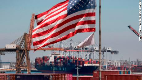 The US flag flies over a container ship unloading it's cargo from Asia, at the Port of Long Beach, California on August 1, 2019. (Photo credit should read MARK RALSTON/AFP/Getty Images)