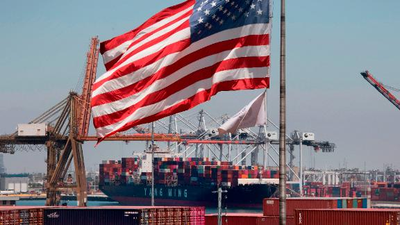 The US flag flies over a container ship unloading it