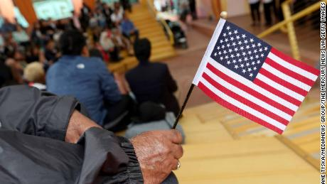OAKLAND, CA - JULY 29: A man holds a flag during a children's citizenship ceremony at Children's Fairyland in Oakland, Calif., on Monday, July 29, 2019. The U.S. Citizenship and Immigration Services San Francisco Field Office swore in 24 kids from 16 countries. (Photo by Jane Tyska/MediaNews Group/The Mercury News via Getty Images)