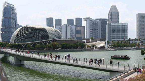 Visitors walk along the bridge leading to the Merlion park in Singapore.