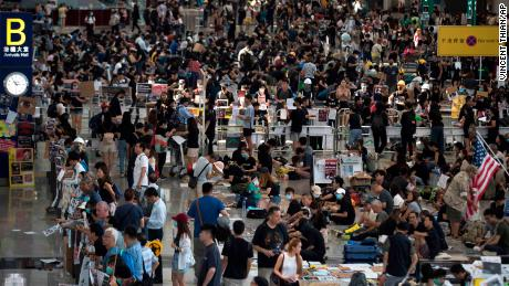 Protesters stage a sit-in rally at the arrival hall of the Hong Kong International Airport in Hong Kong, Tuesday, Aug. 13, 2019. Protesters clogged the departure area at Hong Kong's reopened airport Tuesday, a day after they forced one of the world's busiest transport hubs to shut down entirely amid their calls for an independent inquiry into alleged police abuse. (AP Photo/Vincent Thian)