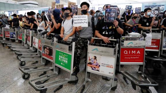 Anti-government protesters stand at a barricade made of trolleys during a demonstration at Hong Kong Airport, China August 13, 2019. REUTERS/Issei Kato