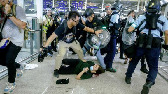 Riot police use pepper spray to disperse anti-extradition bill protesters during a mass demonstration after a woman was shot in the eye, at the Hong Kong International Airport on August 13, 2019.