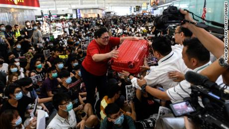 A tourist gives her luggage to security guards as she tries to enter the departures gate during protests on Tuesday.