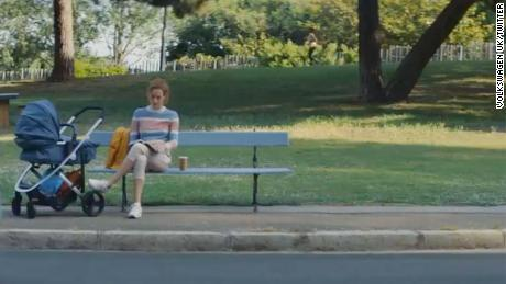 In the Volkswagen ad, a woman is shown sitting by a stroller.