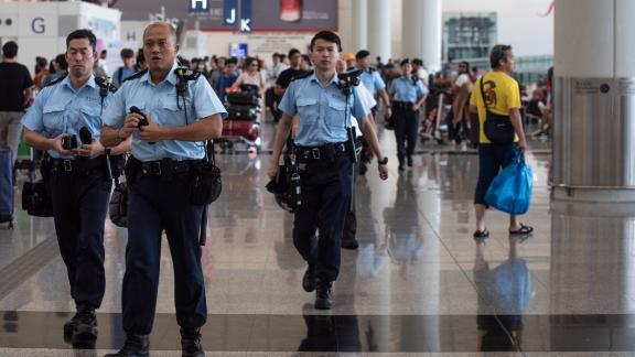 Police officers patrol in the departures hall of Hong Kong
