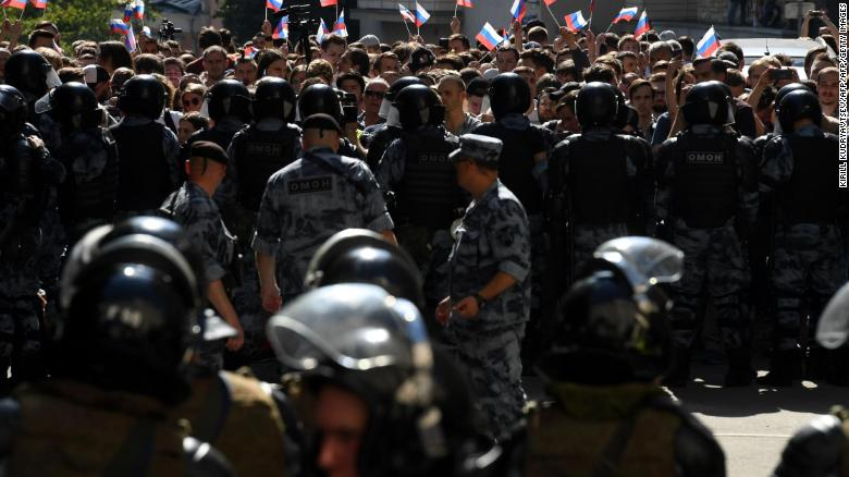 Protesters wave Russian flags as they confront riot police in Moscow.