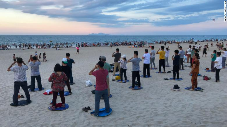 Locals gather for a tai chi and swimming on My Khe beach in Da Nang, Vietnam. During the Vietnam War, the Americans called this China Beach.