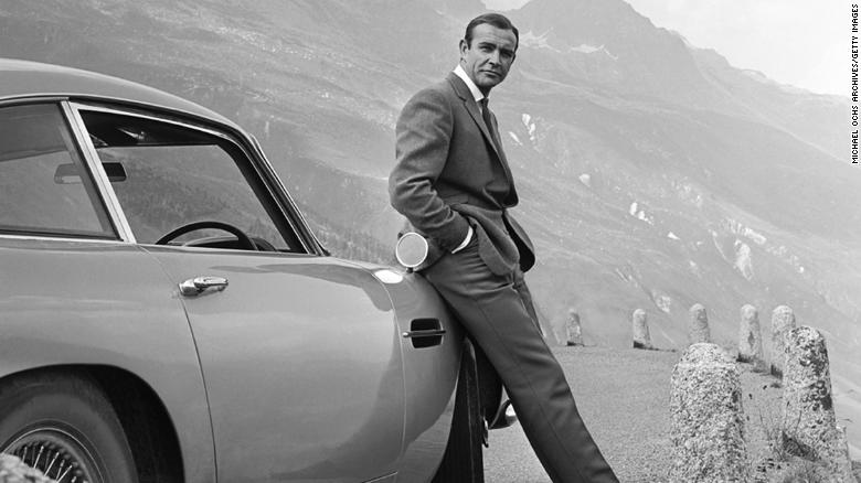Actor Sean Connery poses as James Bond with his Aston Martin DB5 in a scene from the movie 'Goldfinger' in 1964.